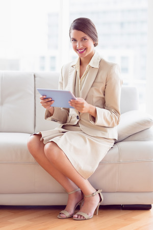 Happy businesswoman sitting on sofa using tablet pc in the office photo