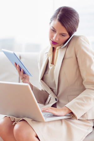 multi tasking: Busy businesswoman sitting on sofa multi tasking in the office Stock Photo