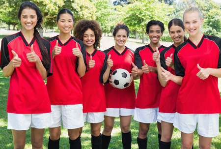 Portrait of successful female soccer team gesturing thumbs up at park