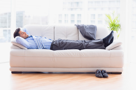 Tired businessman sleeping on a sofa in the office Banco de Imagens