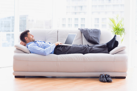 Businessman lying on sofa using his laptop in the office