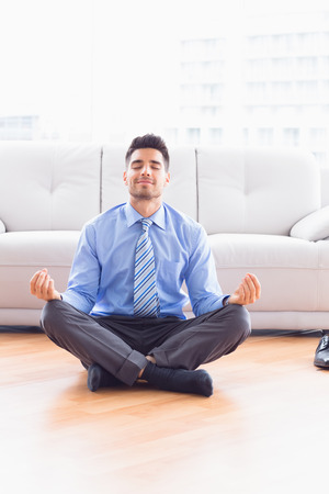 Handsome businessman meditating in lotus pose on the floor in the office photo