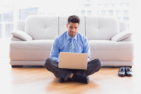 Businessman sitting on floor using laptop in the office photo