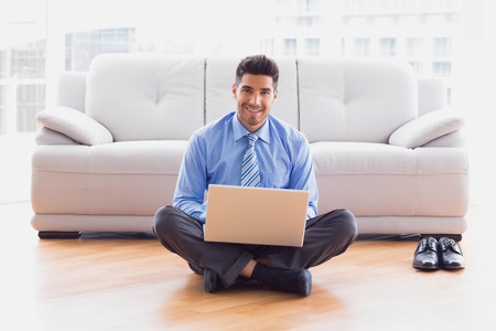 Businessman sitting on floor using laptop smiling at camera in the office photo