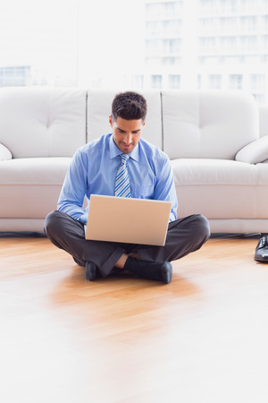Happy businessman sitting on floor using his laptop in the office photo