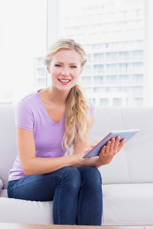 Happy blonde sitting on her sofa using her tablet pc at home in the living room photo