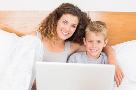 Pretty mother and son sitting on bed using laptop at home in bedroom photo