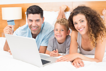 Smiling young family using laptop to shop online together on bed at home in bedroom