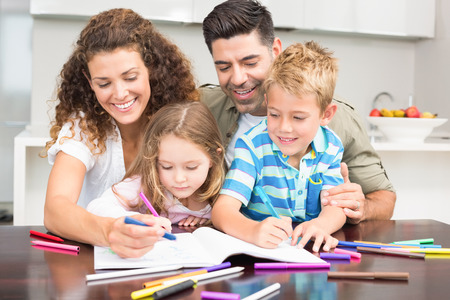 Happy parents colouring with their children at the table at home in kitchen photo