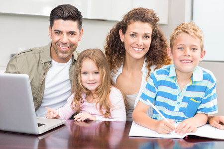 Happy parents colouring and using laptop with their young children at home in kitchen photo