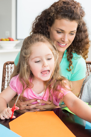 Cheerful little girl doing arts and crafts with mother at the table at home in kitchen photo