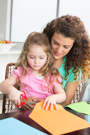 Cheerful little girl cutting paper with mother at the table at home in kitchen photo