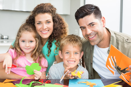 Happy young family doing arts and crafts at the table at home in kitchen photo