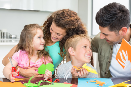 Smiling young family doing arts and crafts at the table at home in kitchen photo