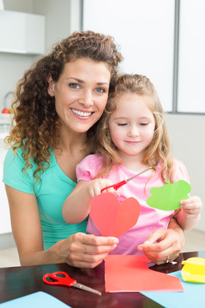 Cute little girl cutting paper shapes with mother at the table at home in kitchen photo