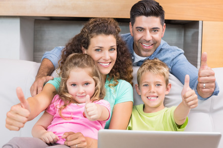 woman laptop happy: Happy family sitting on sofa using laptop giving thumbs up at home in living room
