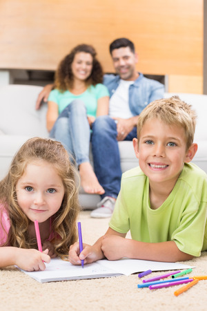 Happy siblings colouring on the rug with parents watching from sofa at home in living room photo
