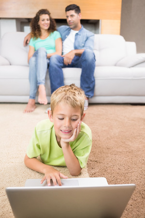 Cute little boy using laptop on the rug with parents sitting sofa at home in living room photo