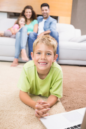 Smiling little boy using laptop on the rug with parents sitting sofa at home in living room photo
