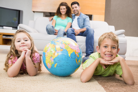 Smiling siblings lying on the rug with a globe at home in living room Stock Photo