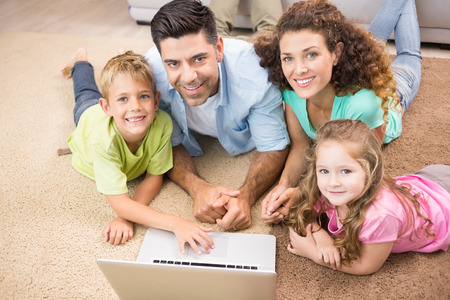 Happy siblings lying on the rug using laptop with their parents at home in living room photo