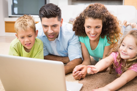 Cute siblings lying on the rug using laptop with their parents at home in living room photo