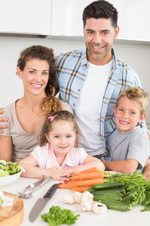 Smiling family preparing vegetables together at home in kitchen photo