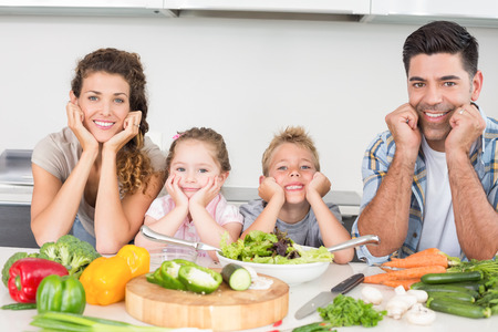 Cheerful family preparing vegetables together at home in kitchen photo