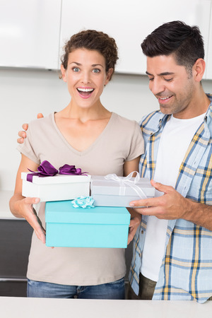 Shocked woman holding many gifts from her partner at home in kitchen photo