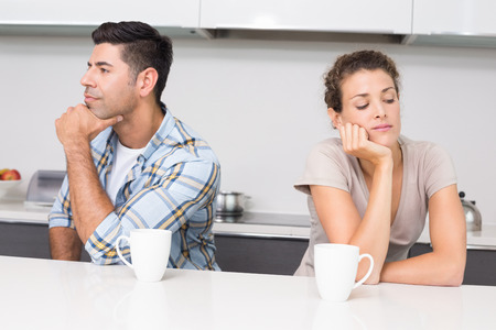 not talking: Unhappy couple having coffee not talking at home in kitchen