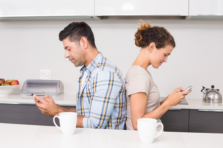 back kitchen: Couple sitting back to back texting at home in kitchen