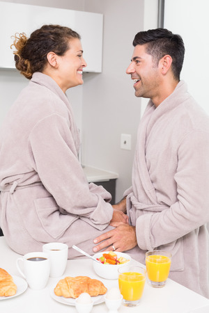 Happy couple in bathrobes having breakfast together at home in kitchen photo