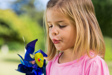 Close-up of cute girl blowing pinwheel at the park photo
