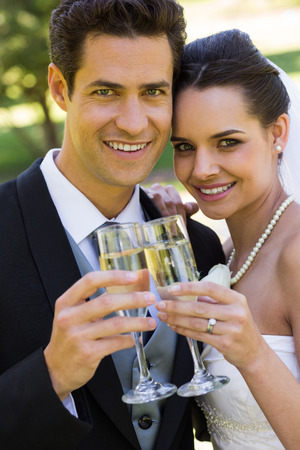 Happy young newlywed couple toasting champagne flutes at the park photo