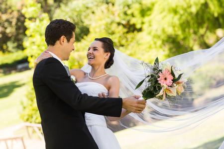 View of a cheerful newlywed couple dancing in the park photo