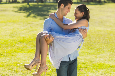 Young man carrying a beautiful woman in the park photo