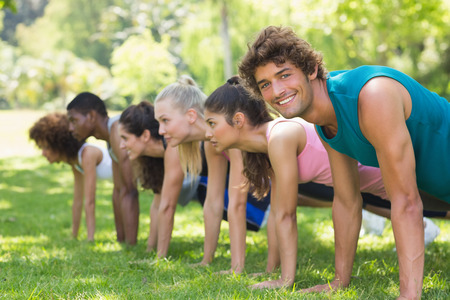 Side view of a group of fitness people doing push ups in the park photo