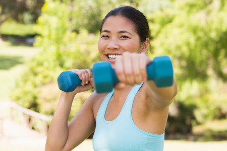 body concern: Close-up of a healthy smiling young woman exercising with dumbbells in the park Stock Photo