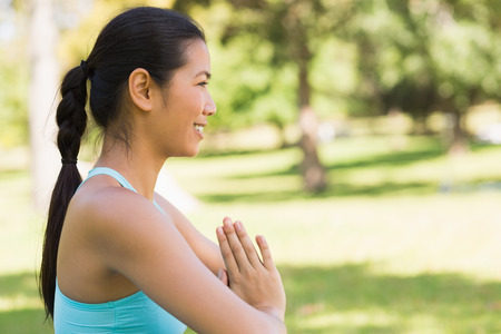 namaste: Side view of a sporty young woman in Namaste position at the park Stock Photo