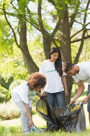 selfless: Team of young volunteers picking up litter in the park Stock Photo