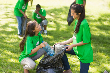 Team of young volunteers picking up litter in the park Imagens