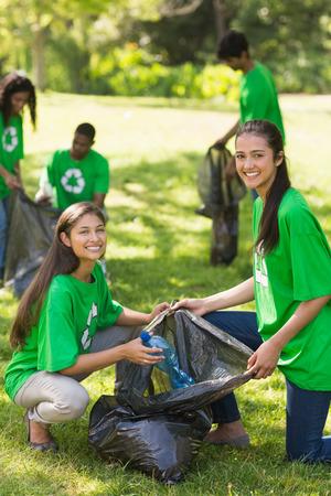 altruism: El equipo de jóvenes voluntarios recogiendo basura en el parque