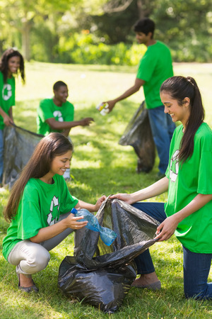 Team of young volunteers picking up litter in the park photo