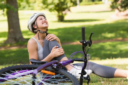 Young female bicyclist with hurt leg sitting on grass in the park photo