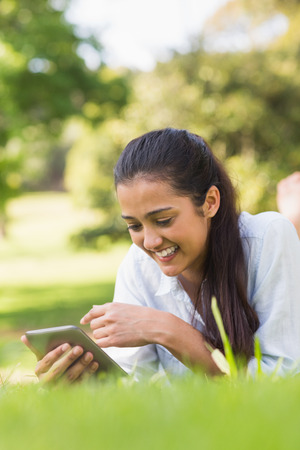 Smiling young woman text messaging while relaxing in the park photo