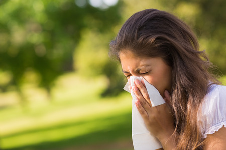 Close-up of a young woman blowing nose with tissue paper at the park photo