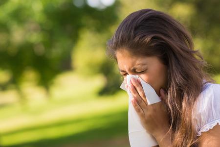 gripe: Primer plano de una joven que sopla la nariz con un pa�uelo de papel en el parque