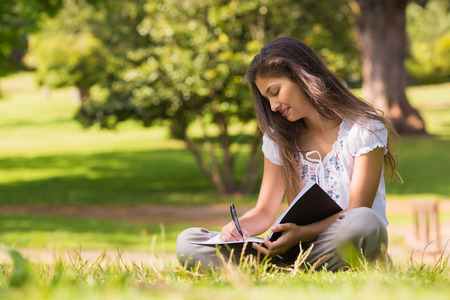 Full length of a young woman with book and pen sitting in the park photo