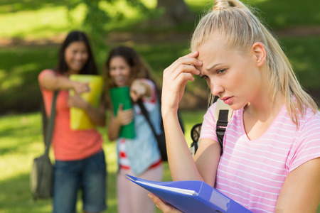 peer pressure: Female student being bullied by other group of students