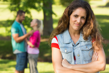 dumped: Portrait of an angry woman with man and girlfriend in background at the park